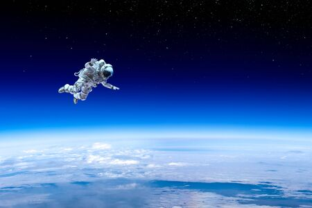 Astronaut in space over Earth planet.