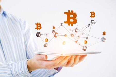 Close of businessman presenting tablet pc and bitcoin icons as concept. 3D rendering