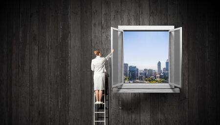 Businesswoman standing on ladder and reaching up opened window in wall. Mixed media