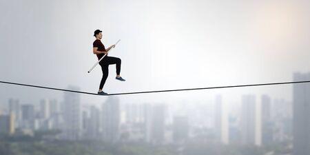Ropewalker in black hat walking rope high in sky . Mixed media Stock Photo