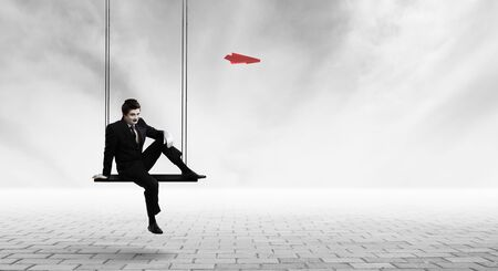 Man mime in black suit sitting on swing. Mixed media Stock Photo