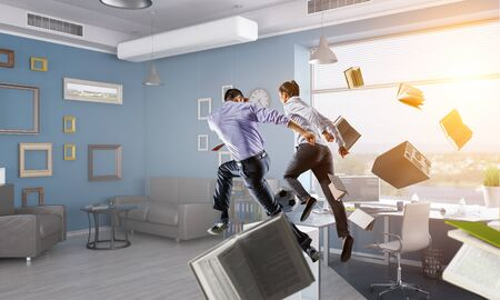Business people play with soccer ball in office. Mixed media Stock Photo