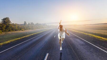 Young sportsman running on asphalt road. Mixed media