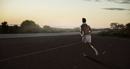 Young athlete running outdoor on countryside road. Mixed media Zdjęcie Seryjne