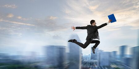 Cheerful businessman jumping high excited about his success. Mixed media