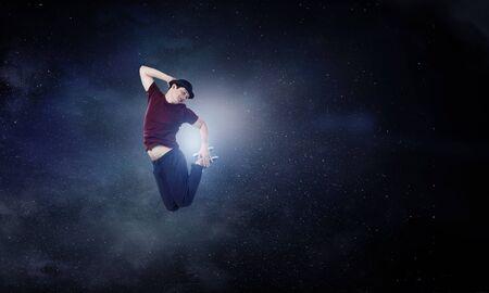 Junge männliche professionelle Tänzer mit Hut springen hoch. Gemischte Medien