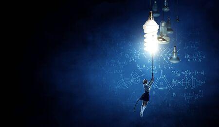 Cheerful kid flying on glowing light bulb. Mixed media