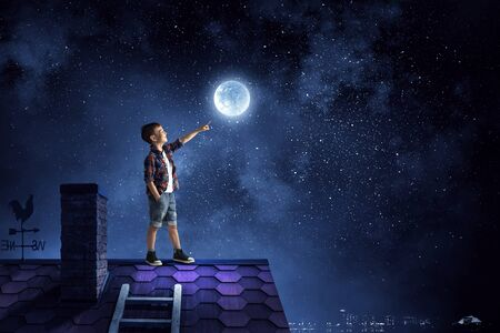 Kid boy of school age touch moon planet