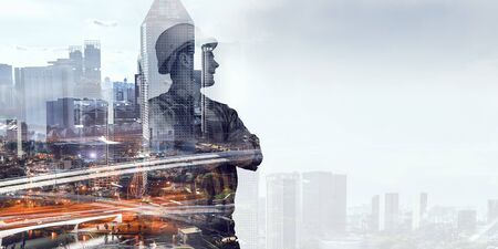 Double exposure of builder man in helmet and modern cityscape