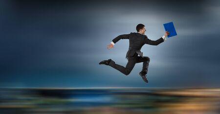 Fröhlicher Geschäftsmann springt hoch aufgeregt über seinen Erfolg. Gemischte Medien