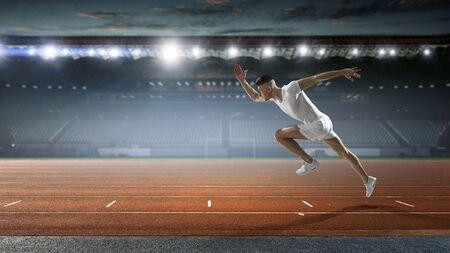 Sportsman running track. Mixed media Reklamní fotografie