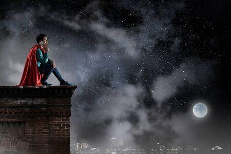 Super hero on roof. Mixed media Reklamní fotografie