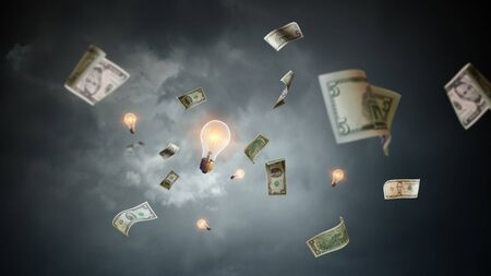 Dollar banknotes fly in air and glass bulb. Mixed media