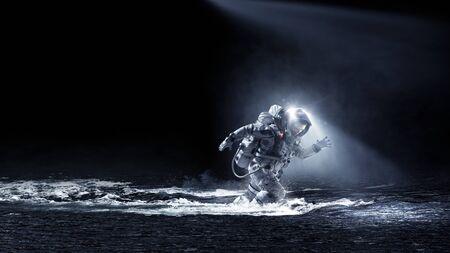 Astronaut in spacesuit running in water. Mixed media Reklamní fotografie
