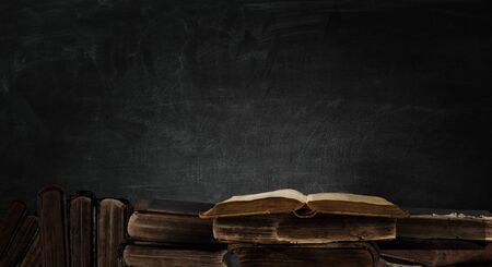 Pile of old books on dark background