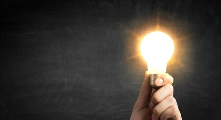 Glowing light bulb in hand as symbol for bright idea 스톡 콘텐츠