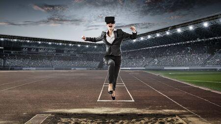 Businesswoman in virtual mask running at stadium. Mixed media