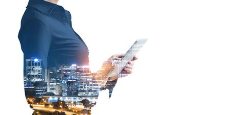 Double exposure of businesswoman with tablet in hands and modern cityscape on white background