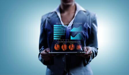 Close of businesswoman holding tablet pc with infographs on screen. Mixed media Archivio Fotografico