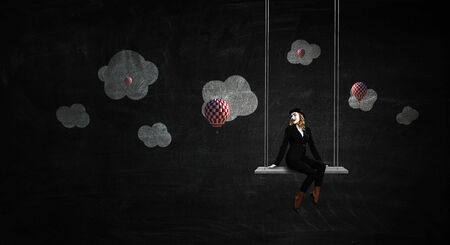 Mime woman in black suit riding swing. Mixed media Reklamní fotografie