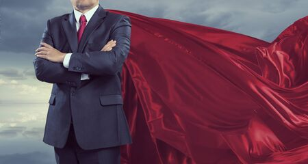 Senior confident businessman in red cape with hands folded on chest . Mixed media Imagens