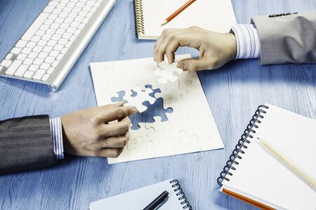 Hand of businesspeople completing puzzle with missing piece Stock Photo