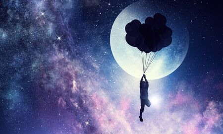 Silhouette of kid boy flying on bunch of balloons in night starry sky. Mixed media Archivio Fotografico