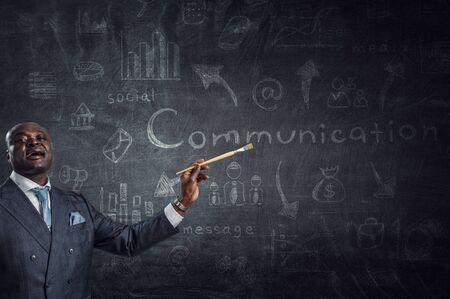 Image conceptuelle d'un homme d'affaires ambitieux et créatif en costume noir tenant un pinceau à la main