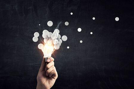 A hand holding pixelated bulb. Development concept. Mixed media