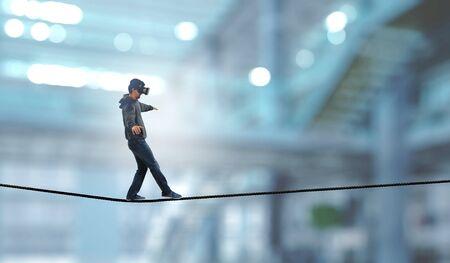 Man wearing virtual reality goggles and balancing on rope