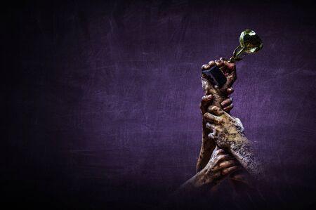 Hand holding up a gold trophy cup against dark background Standard-Bild