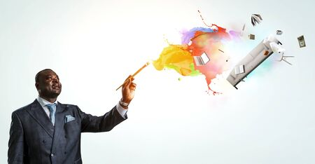 Conceptual image of ambitious and creative businessman in black suit holding paintbrush in hand 版權商用圖片