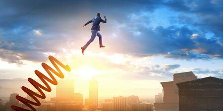 Businessman jumping on springboard as symbol of progress. Mixed media