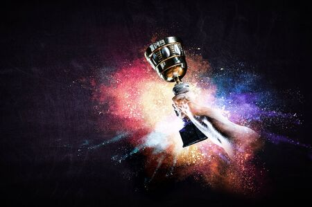Hand holding up a gold trophy cup against dark background Banque d'images