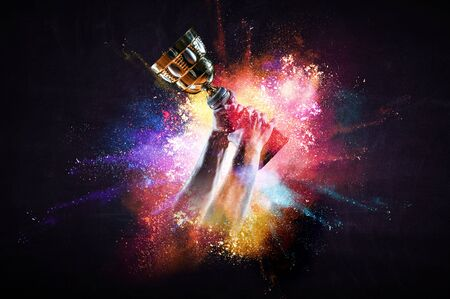 Hand holding up a gold trophy cup against dark background. Mixed media