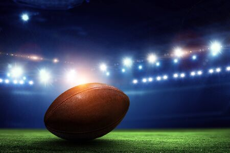 Night football arena in lights and flashes with american football ball on the foreground
