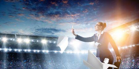 Businesswoman standing against stadium and making selfie Standard-Bild