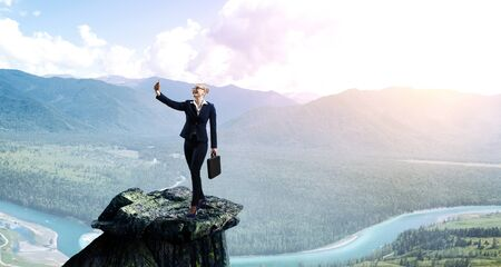 Businesswoman standing against landscape and making selfie