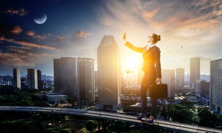 Businesswoman standing against cityscape and making selfie