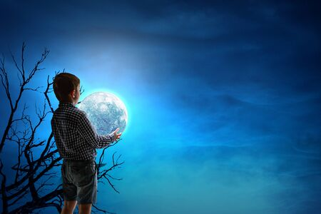 Boy holding moon at night