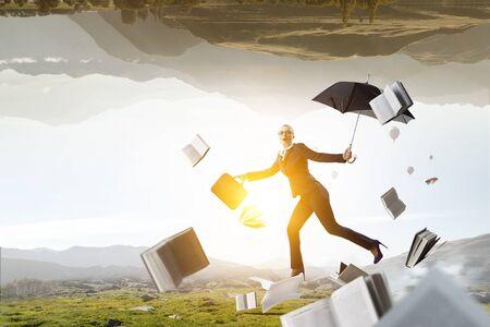 Young businesswoman walking with umbrella Standard-Bild