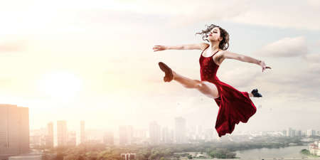 Young and beautiful female dancer in a red dress
