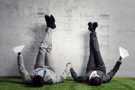Couple of businessmen relaxing with their legs up on wall