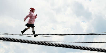 Little girl walking a rope with sky at background