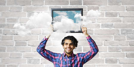 Man holding frame with blue sky and clouds