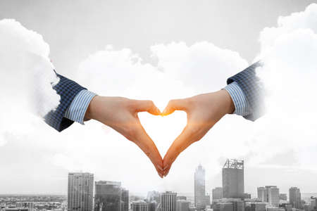 Male hands form heart shape