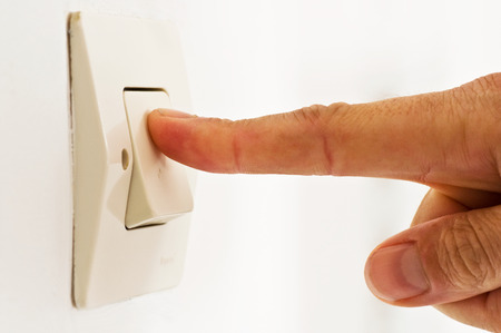 light off - finger on switch closeup photo