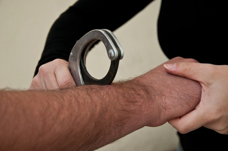 handcuffed: man handcuffed Stock Photo