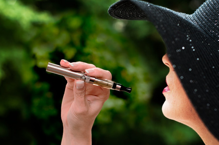 background e cigarette: fashion woman with e-cigarette in outdoor Stock Photo
