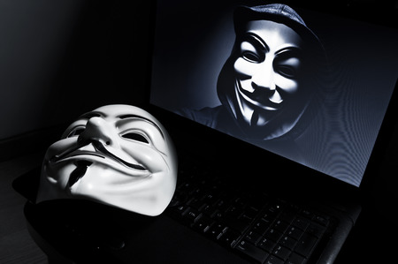 vendetta: Paris - France - 18 January 2015 - Vendetta mask on computeur with an anonymous member on screen, . This mask is a well-known symbol for the online hacktivist group Anonymous